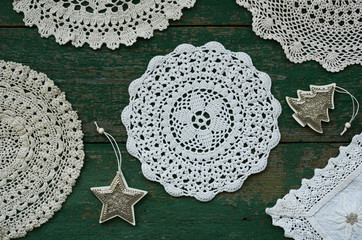 Set of vintage lace doilies and Christmas toys on rustic background