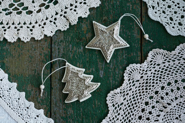 Vintage Christmas toys and lace napkins on green wooden background
