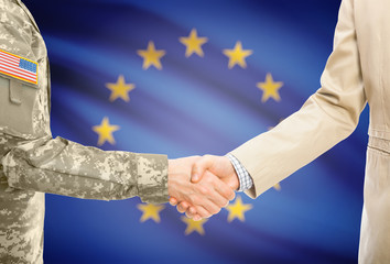 USA military man in uniform and civil man in suit shaking hands with adequate national flag on background - European Union