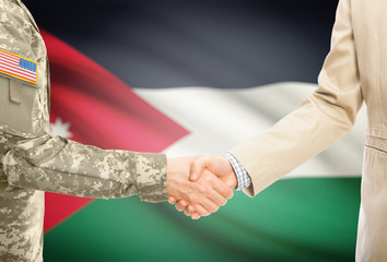 USA military man in uniform and civil man in suit shaking hands with adequate national flag on background - Jordan