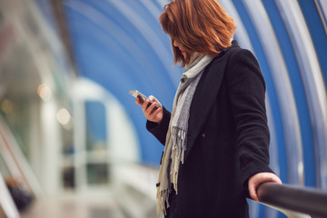 Photo of woman in black coat with phone in hands standing in modern building