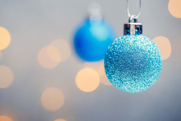 Image of two Christmas blue balls on gray background with spots.