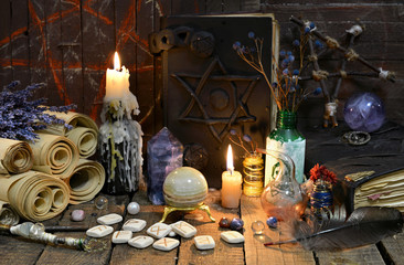 Black magic book with old runes, manuscripts and crystals. Occult, esoteric, divination and wicca concept. Mystic and vintage background