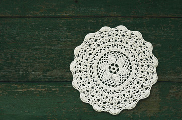 Winter background - snowflake like crocheted vintage doily with copy space on green wooden surface