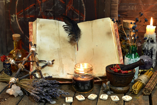 Old witch book with empty pages, lavender flowers, pentagram and witchcraft objects. Occult, esoteric, divination and wicca concept. Mystic and vintage background