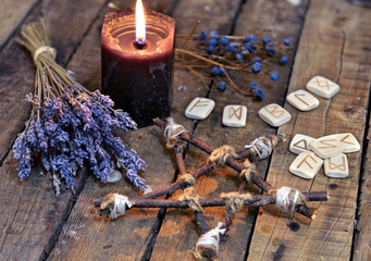Pentagram with lavender flowers, old runes and black candle on planks. Occult, esoteric, divination and wicca concept. Mystic and vintage background