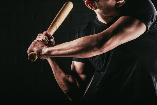 partial view of young sportsman playing baseball with bat isolated on black