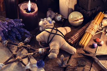 Voodoo doll, pentagram and magic objects on witch table. Occult, esoteric, divination and wicca concept. Mystic, voodoo and vintage background