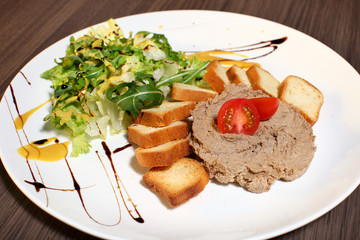 Slice of toasted bread and liver pate on white plate