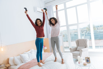 No time for worries. Full length shot of two curly haired ladies in casual beaming while holding video game consoles and jumping high on a bed.