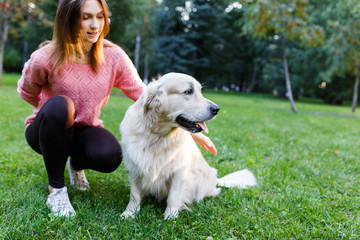 Photo of brunette with labrador lying on lawn in summer park