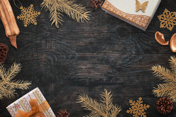 Christmas gold color decorations on black wooden board. Free space in the middle for text. Top view.