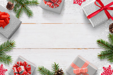 Christmas New Year background with gifts and free space for text. White wooden board with Christmas tree branches, pinecones, and snowflake decorations.