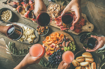Flat-lay of friends eating and drinking together. Top view of people having party, gathering, dinner together sitting at wooden rustic table set with wine snacks and fingerfoods. Hands with glasses