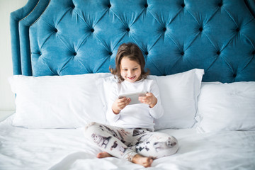 child, technology and internet concept - little girl lying in bed with smartphone and play games at home