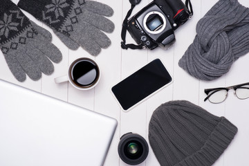 Men's winter casual outfits with camera, coffee cup, laptop, smartphone and eyeglasses on wooden background