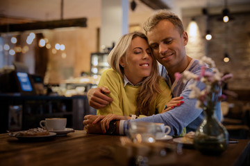 Couple embracing in cafe