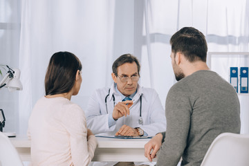 wife and husband listening doctor at clinic