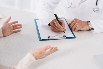cropped image of doctor writing down something to clipboard after patient