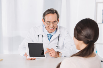 doctor showing something on tablet to female patient