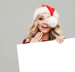 Happy Surprised Christmas Woman Fashion Model holding White Paper Card Background. Smiling Woman in Santa Hat