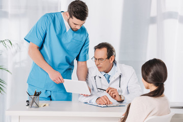 male nurse showing something to doctor on tablet