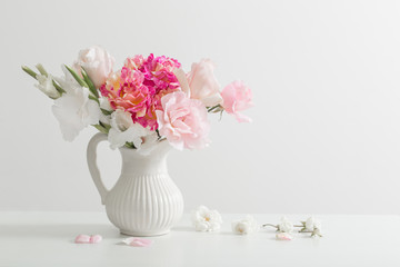 pink and white flowers in vase on white background