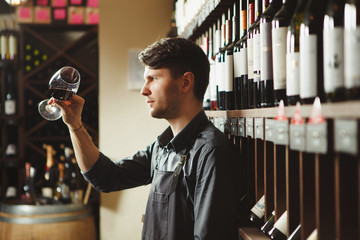 Bartender looks at red wine in glass in cellar