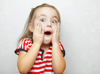 Surprised little girl with open mouth and hands on cheeks