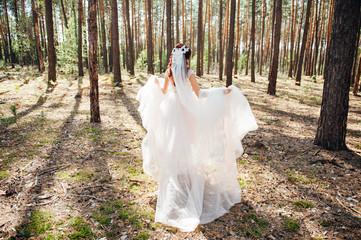 Bride in white wedding dress walking in forest.