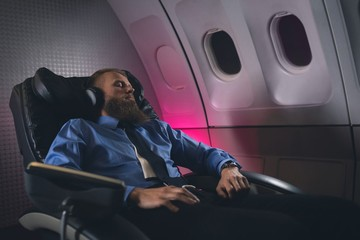 Businessman sleeping on seat in airplane