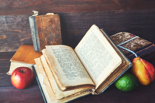 open book and apples over dark wooden background