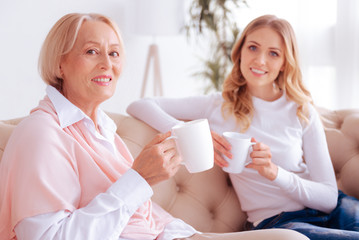 Its tea time. Delighted positive elderly woman holding a cup of tea and smiling while sitting together with her daughter