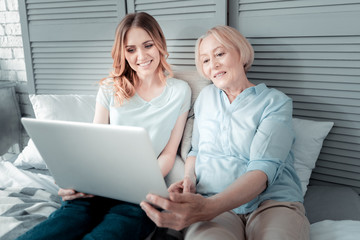 Modern device. Joyful nice pleasant women sitting together and looking at the laptop screen while resting at home