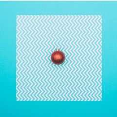 Red Christmas decoration ball on blue background. New Year concept