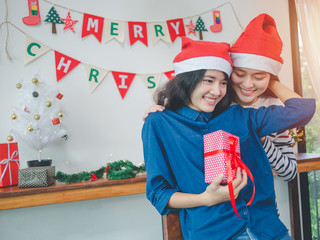 Two asian women Lesbian couple holding gift box in christmas party, Have christmas tree ornaments.