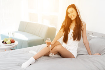 A girl in a veil sits on the bed. Brunette posing for a photo in a white tank top and veil