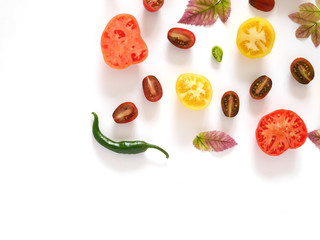Food collage of fresh vegetables, top view. Tomatoes in a cut, pepper, autumn leaves isolated on white background. Abstract composition of vegetables, concept of healthy eating.