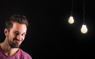 Unentschlossener junger Mann neben Glühbirnen