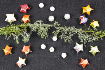 Paper stars, white pearls and tree branch of different colors on a black background