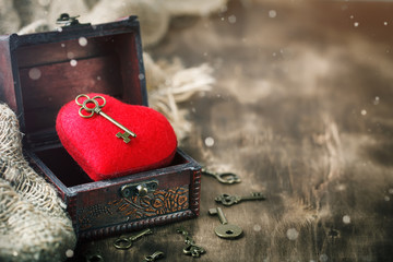 Valentine's day background with a heart and an ancient key on wooden table.