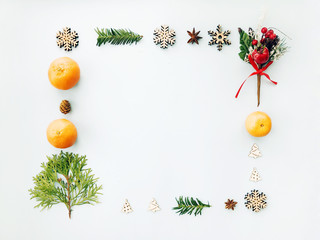 Christmas composition or frame. Christmas decorations, mandarins, fir tree branches on light background. Top view with copy space, flat lay.