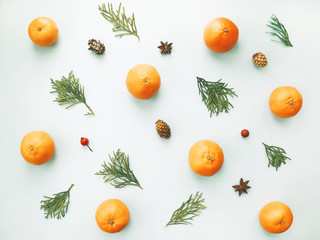 Christmas composition. Pattern made of pine branches and mandarins on light background. Flat lay, top view. Layout for Christmas card.
