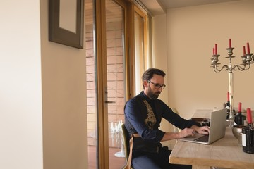 Man in well dressed using laptop on dining table