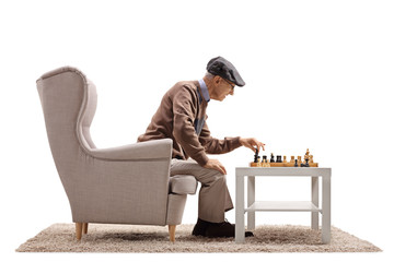 Elderly man sitting in an armchair and playing chess with himself