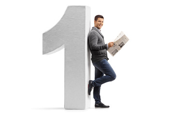 Man with a newspaper leaning against a cardboard number one