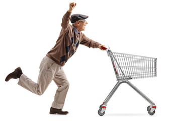 Joyful senior with 3D glasses running and pushing an empty shopping cart