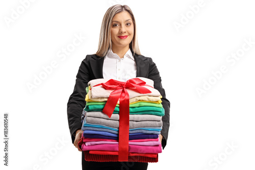 Formally Dressed Woman Holding A Stack Of Clothes Wrapped With Red