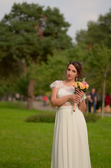 Incredibly beautiful bride with bouquet of roses. Romantic accessory of fiancee. Long haired girl in wedding gown