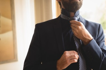 Man wearing his tie at home